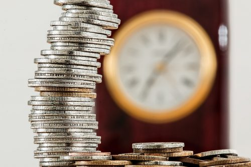 The fine art of monetizing minimalism: Photo of a stack of coins in front of a clock.
