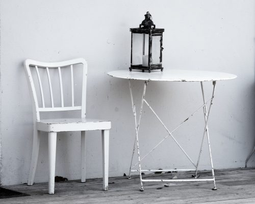 Make space for the in-bewteens: B&W photo of old metal table and chair outdoors.