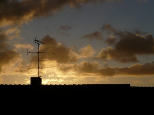 Media diet: Photo of TV antenna on roof in sunset.