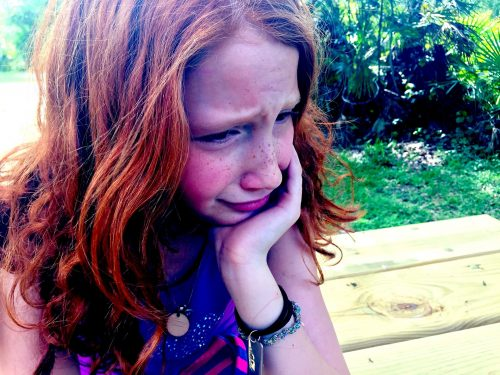 Beat the grief of letting go of stuff: Photo of redhead girl crying.