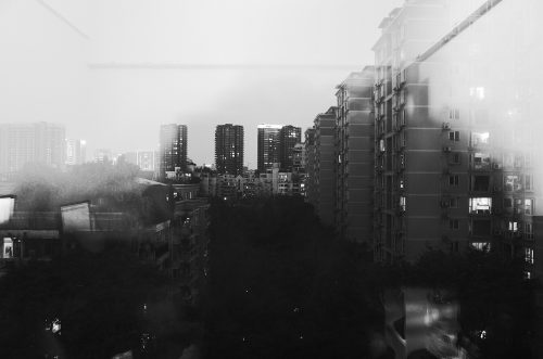 Transformable apartments: Distorted black and white photo of city scape.
