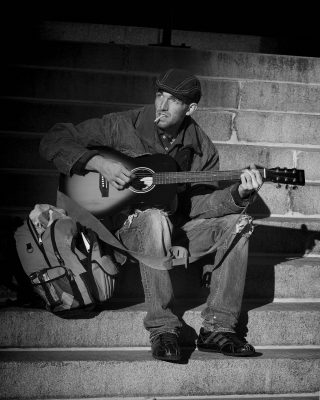 Consumerism: Photo of homeless street musician.