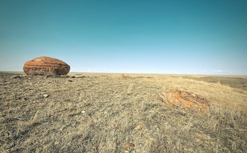 Cluttered thoughts: Photo of a single large rock in a barren desert.