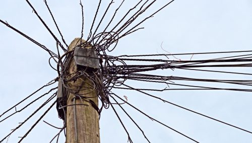 Disconnected: Photo of telephone pole with dozens of wires.