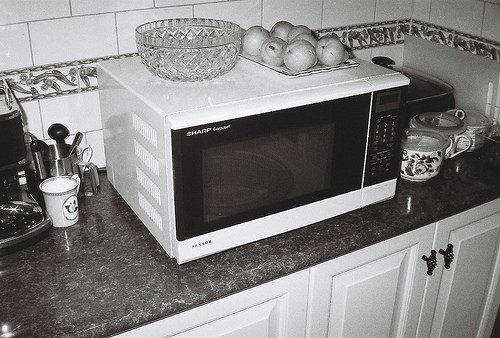19268622470_68463778f6 7 reasons to stop using a microwave: Photo of old microwave on kitchen counter.