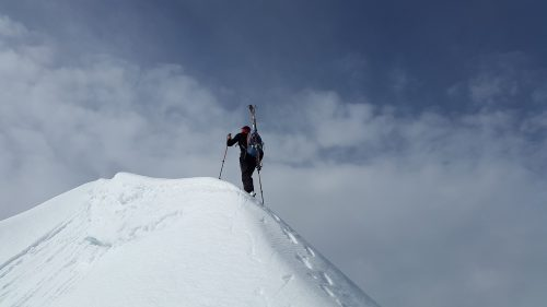 Resolutions are setting you up for failure again and again: Photo of man at top of mountain peak.