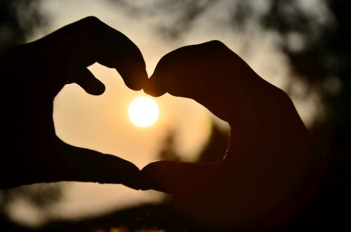 10 beautiful outcomes of living simply: Photo a sunset through hands making a heart .